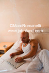 Stock photo of a man shopping the web on his laptop at home.  He is dressed in a white tank top t shirt and white pants. He is bald and laying on his bed.